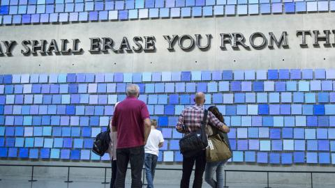 "Five Museum visitors stand with their backs to the camera in Memorial Hall, observing two site-specific artworks. A quotation forged from recovered World Trade Center —""No day shall erase you from the memory of time""—speaks to the Museum's promise to remember the 2,983 lives lost on 9/11 and in the 1993 bombing. Surrounding the letters of the Virgil quote is a work by artist Spencer Finch titled Trying to Remember the Color of the Sky on That September Morning."
