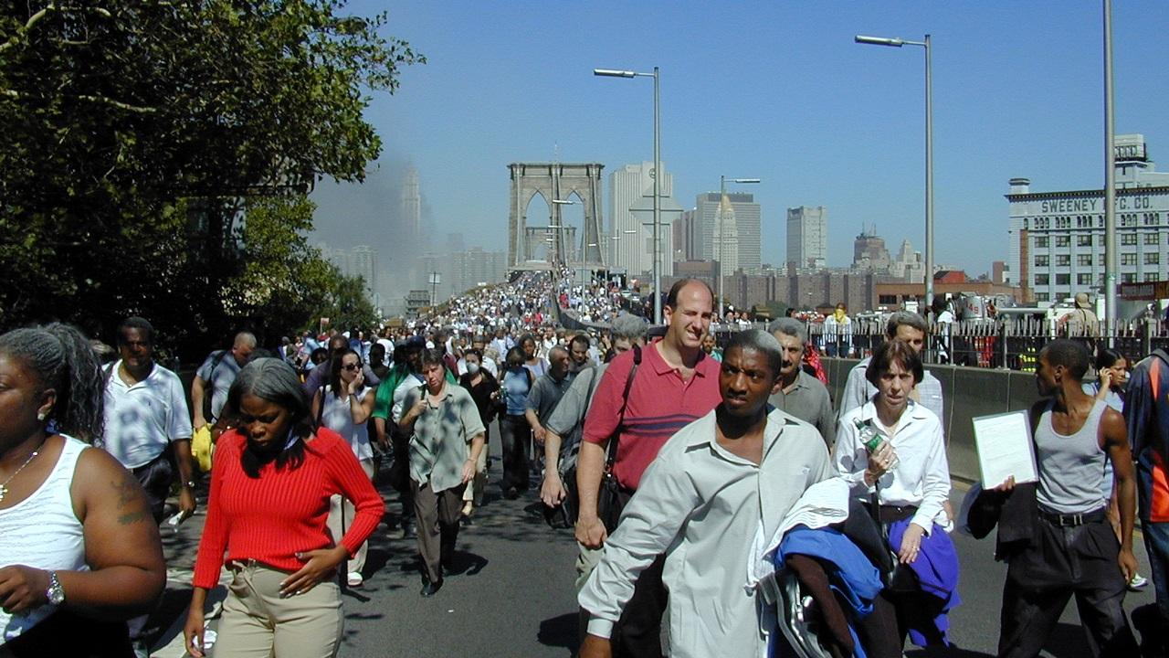 Dozens of people approach after walking across the Brooklyn Bridge on September Eleventh. They have dust and soot from the World Trade Center in their hair. Behind them, hundreds more people cross the bridge. In the distance is the skyline of lower Manhattan, with a cloud of smoke hovering over downtown.