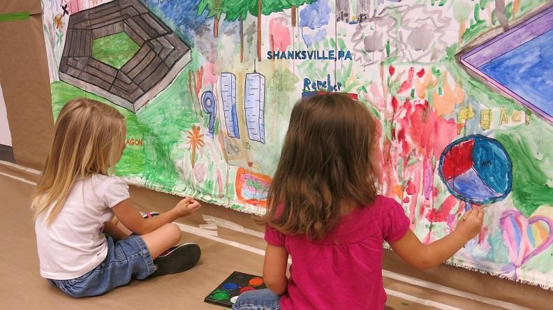 Two young girls sit on the floor as they paint a mural about the events of 9/11. They share a paint palette as they brush a colorful picture that features the Pentagon, Twin Towers, trees and hearts.