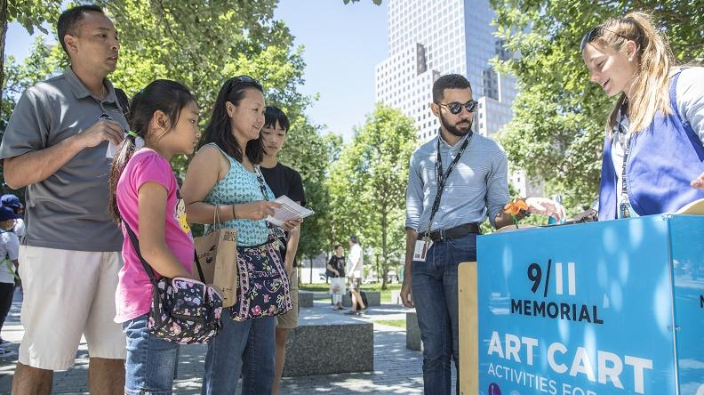 A man, woman, boy, and girl watch as two Museum employees display artwork at the Art Cart on the Memorial. It's a warm day and sunshine falls on the trees and buildings in the background.