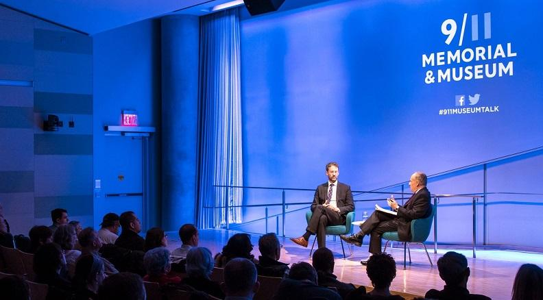 Two men take part in a discussion at the Museum. The auditorium is lit blue and spotlight is on the two men as they sit on stage. Silhouetted audience members watch from the left.