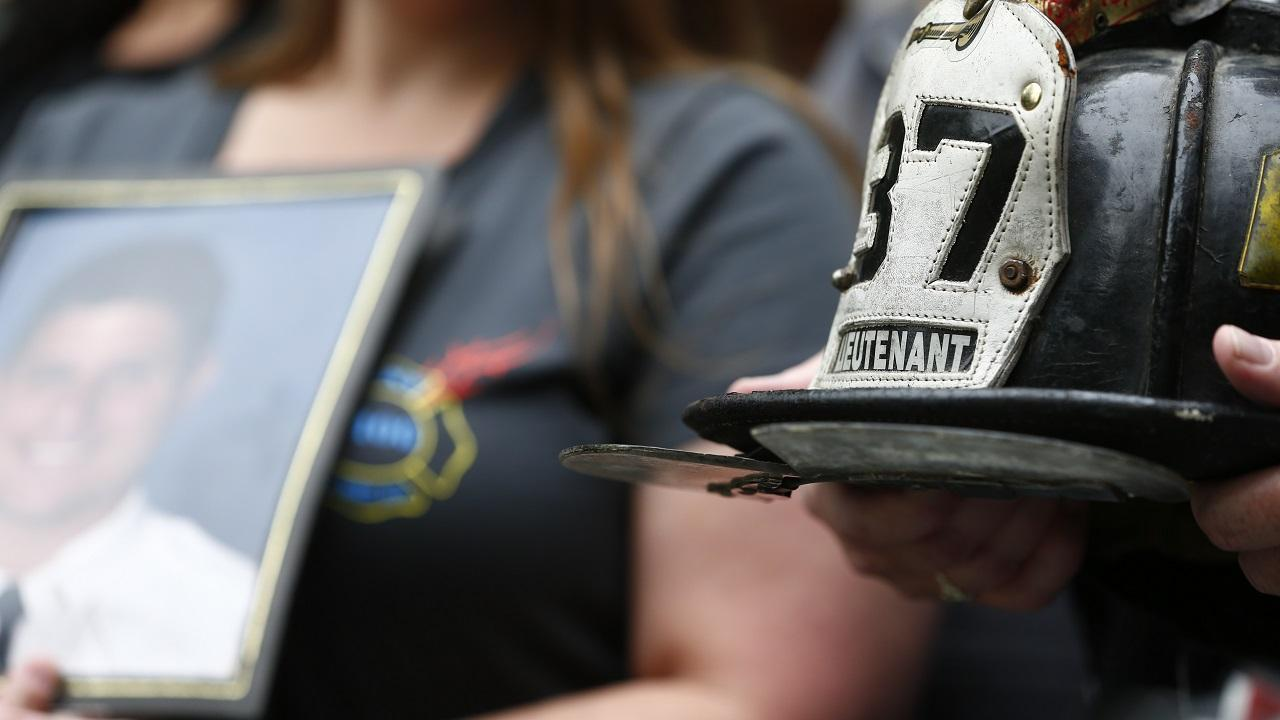 In focus to the right are two hands holding a firefighter helmet with the number 37 and the word lieutenant on it. Out of focus to the left is a woman holding a framed photo of a man.