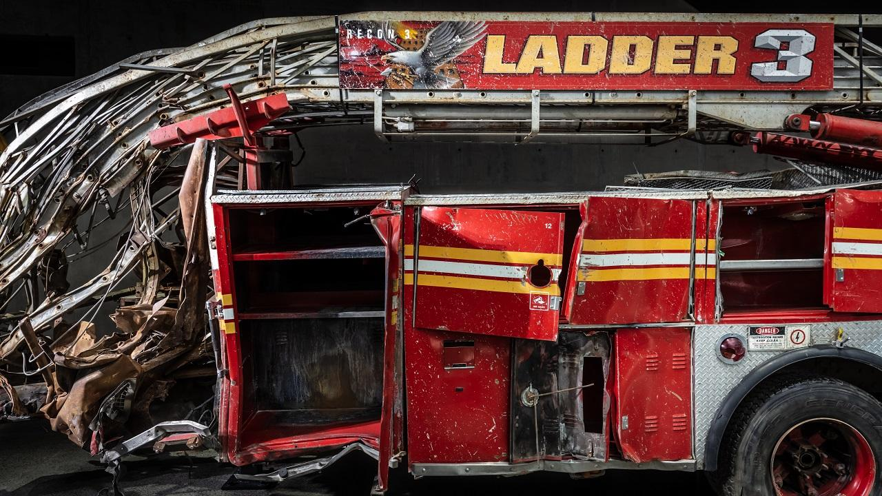 The heavily damaged firetruck of FDNY Ladder Company Three sits in the Museum. This close-up view shows the bright red vehicle's twisted ladder and broken compartment doors.