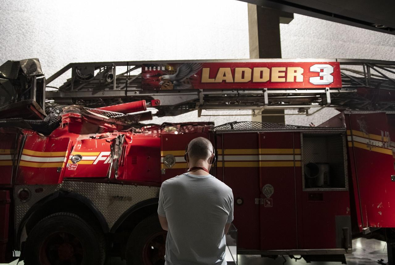 A museum visitor stands with his back to the camera in front of the Ladder 3 firetruck in the museum.