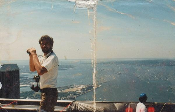 Stephen Knapp holds a pair of binoculars on the rooftop of the North Tower in this old photo. The South Tower can be seen off to the left. Aerial views of New York Harbor and the Atlantic Ocean are seen to the right.