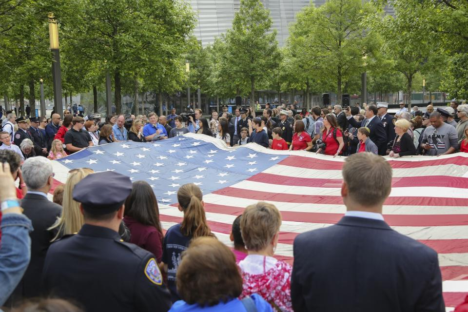 Dozens of people stand in Memorial plaza as they hold up a large American flag during the opening of the Museu in May 2014.