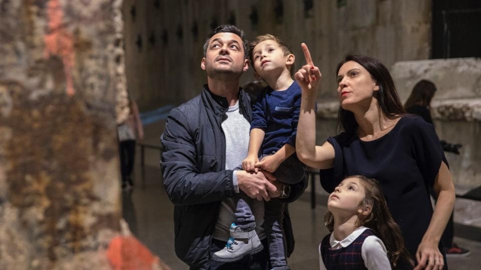 A man and woman stand with two a young boy and girl at the Museum. The man is holding the boy as the woman stands with the girl by her side. All four of them are looking up at the Last Column as the woman points up at it.