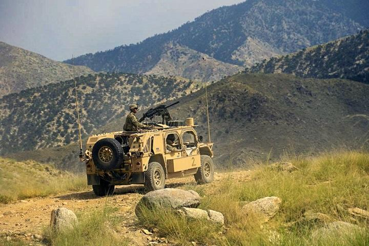 A soldier looks out from a humvee vehicle with green, rolling hills and mountains in the background.
