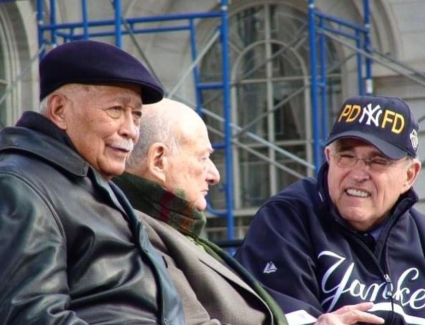 In this group photograph taken at City Hall in 2009, three former mayors are shown together from the waist up.   Mayor Dinkins, wearing a black cap and jacket, is looking ahead while Mayor Koch engages with Mayor Rudy Giuliani .