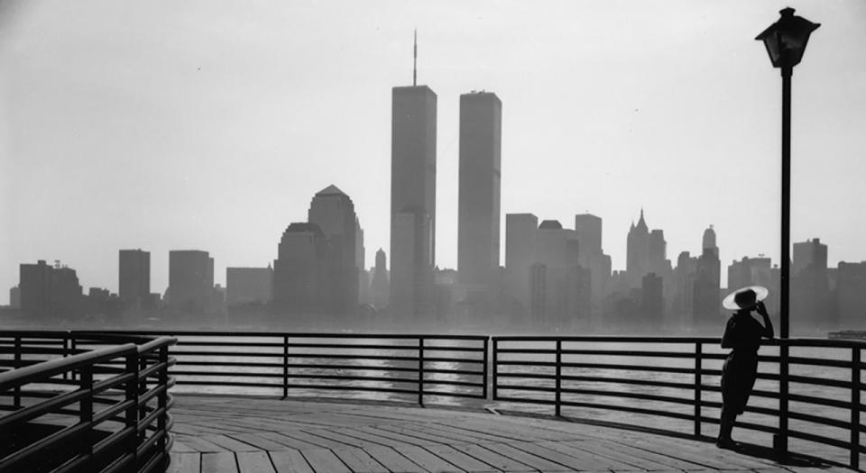 A woman in silhouette leans against a lamppost on a curved boardwalk, facing the view of lower Manhattan in the background. The Twin Towers, at the center of the skyline, rise into the cloudy sky.